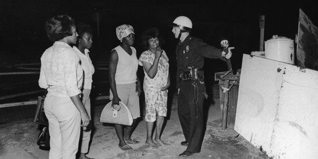 A policeman guides a group of women to safety during rioting in the Watts area of Los Angeles, August 1965. Their homes have