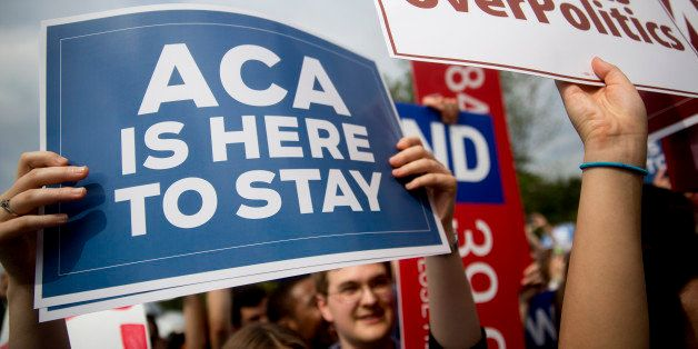 A demonstrator in support of U.S. President Barack Obama's health-care law, the Affordable Care Act (ACA), holds up a 'ACA is