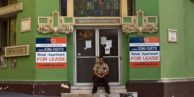 A private security guard sits in front of a closed down business in the colonial district of Old San Juan, Puerto Rico, Sunda