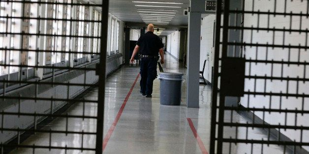 A Rikers Island juvenile detention facility officer walks down a hallway of the jail, Thursday, July 31, 2014, in New York. (