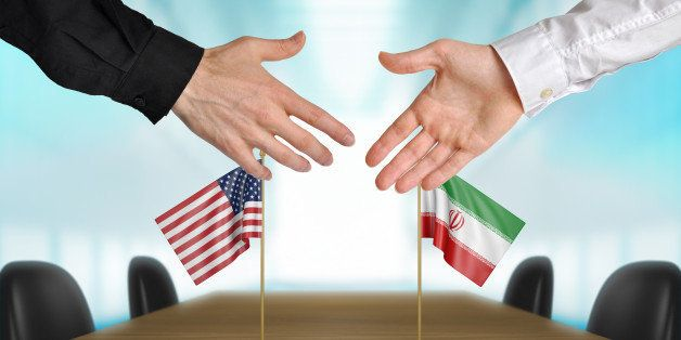 Two diplomats from the United States and Iran extending their hands for a handshake on an agreement between the countries.