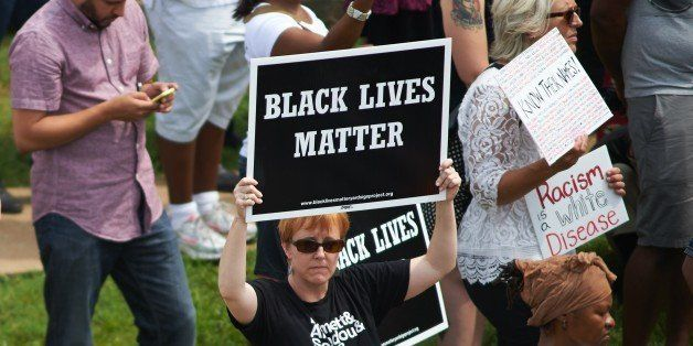 A woman holds a 'Black Lives Matter' sign during a memorial service for slain 18 year-old Michael Brown Jr. on August 9, 2015