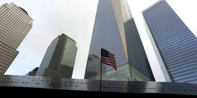 An American flag marks the name of a loved one at the North Pool Memorial site in front of 1 World Trade Center during memori