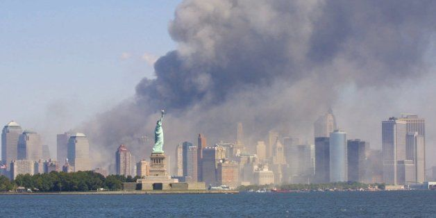 The Statue of Liberty stands as smoke billows from the World Trade Center in New York, Tuesday, Sept 11, 2001 after terrorist