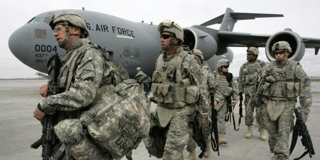 US soldiers arrived from Afghanistan walk outside a plane at the US airbase 30 km outside Bishkek in Manas on February 26, 20