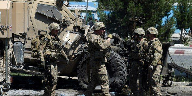 NATO soldiers arrive at the scene of a suicide car bomb attack that targeted foreign military vehicles in Kabul on June 30,20