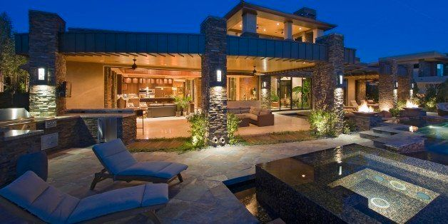 House exterior lit up at night, with patio furniture