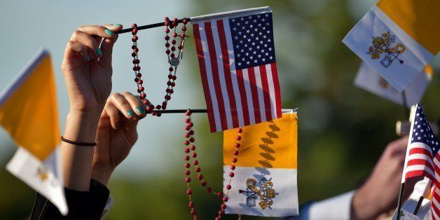 People wave US and Vatican flags as they wait for the arrival of the Pope Francis at the White House in Washington DC on Sept