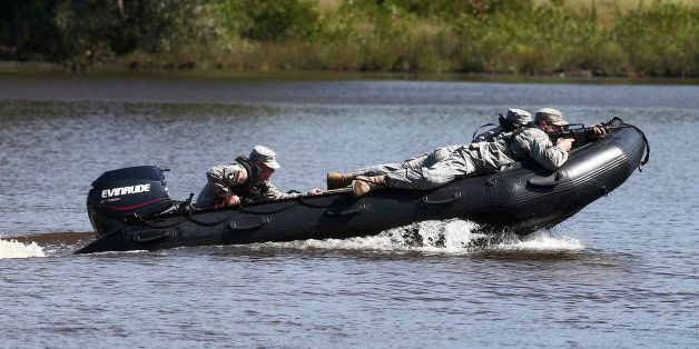 U.S. Army rangers demonstrates watercraft skills during a Army Ranger school graduation Friday, Aug. 21, 2015, in Fort Bennin