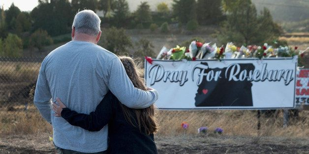 ROSEBURG, OR - OCTOBER 03:  Dave (L) and Robin Griffiths leave flowers at a memorial along the road to Umpqua Community Colle