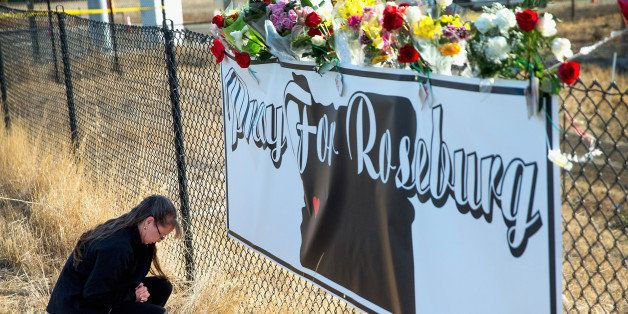 ROSEBURG, OR - OCTOBER 03:  Robin Griffiths leaves flowers at a memorial along the road to Umpqua Community College on Octobe