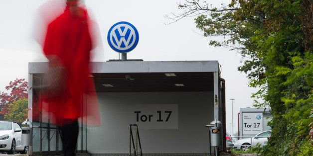 A VW employee enters the Volkswagen factory site through Gate 17 in Wolfsburg, Germany, Oct. 6, 2015. For Volkswagen, the cos