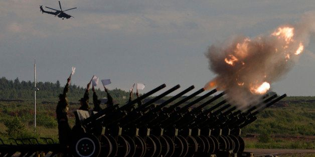 Russian Army's MI-28 attack helicopter flies as salute cannons fire during a show at a shooting range in Alabino, outside of