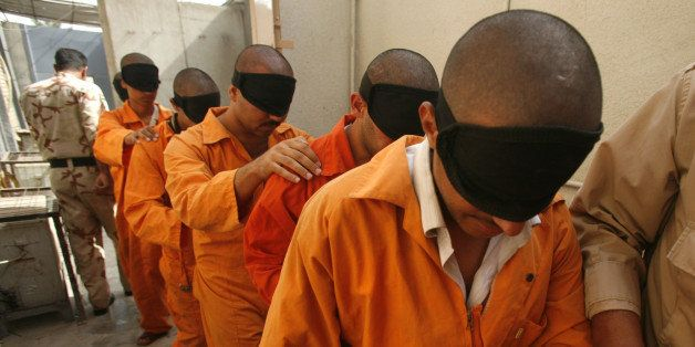 In this Aug. 11, 2007 file photo, blindfolded prisoners are taken for questioning at the Iraqi National Police Detention Cent