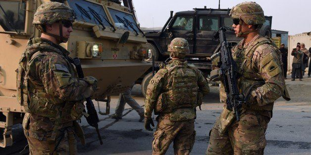 US soldiers stands guards at the scene of a suicide car bomb attack on a European Union police vehicle along the Kabul-Jalala