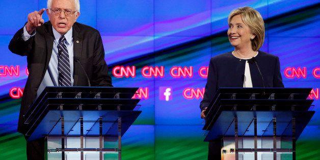 Sen. Bernie Sanders, of Vermont, left, speaks as Hillary Rodham Clinton looks on during the CNN Democratic presidential debat