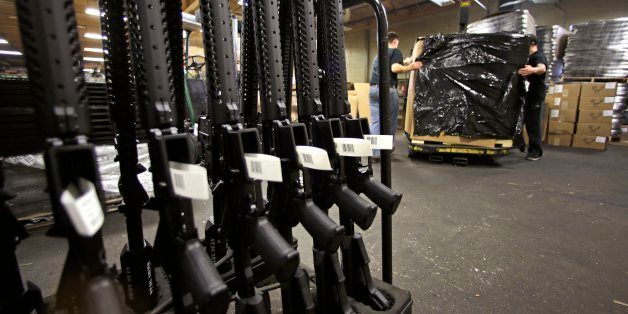 A rack of AR-15 rifles stand to be individually packaged as workers move a pallet of rifles for shipment at the Stag Arms com