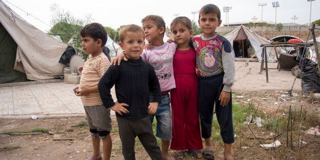 In this photo taken on Friday, Oct.  23, 2015, Children stand at a refugee camp in Latakia, Syria. Latakia, the heartland of