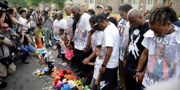 CORRECTS CITY TO FERGUSON Michael Brown Sr. along with family and friends stop to pray at a memorial to Brown's son before ta