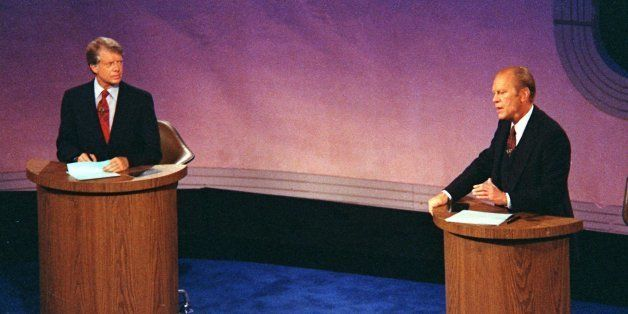 President Gerald Ford speaks as Jimmy Carter listens during the first of three televised debates in September 23, 1976, held