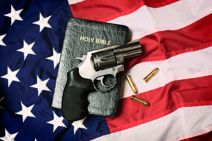A handgun resting on a Bible and an American flag, representing the Second Amendment of the US Constitution, the right of pat