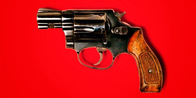 Hand gun against red background, close-up