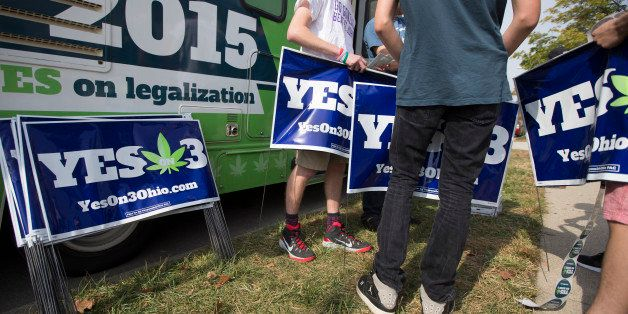 College students collect lawn signs at a promotional tour bus from ResponsibleOhio, a pro-marijuana legalization group, at Mi