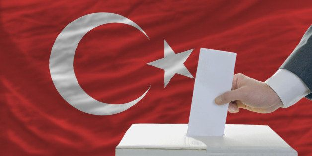 man putting ballot in a box during elections in turkey in front of flag