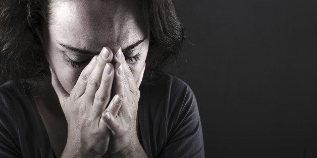 Depressed woman on black background