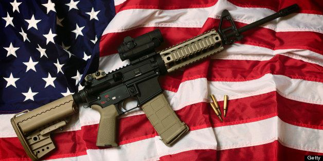 An AR-15 rifle with bullets on an American flag, a symbol of the right of patriotic Americans to bear arms, guaranteed by the