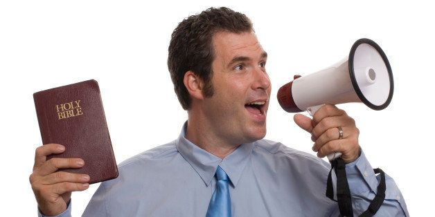Young caucasian male yelling into megaphone while holding Holy Bible in other hand.  He is wearing a blue shirt and blue tie.
