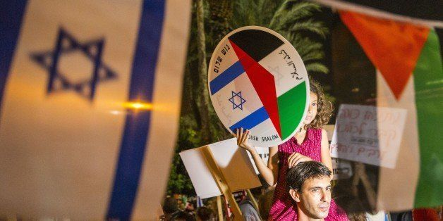 A young girl holds a bearing images of the Israeli and Palestinian flags during a Israeli left-wing activist rally demanding