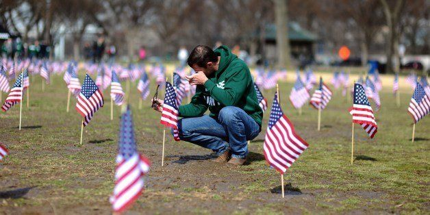 US Navy Iraq war veteran Jeff Hensley wipes his tears as he helps set up 1,892 American flags on the National Mall in Washing