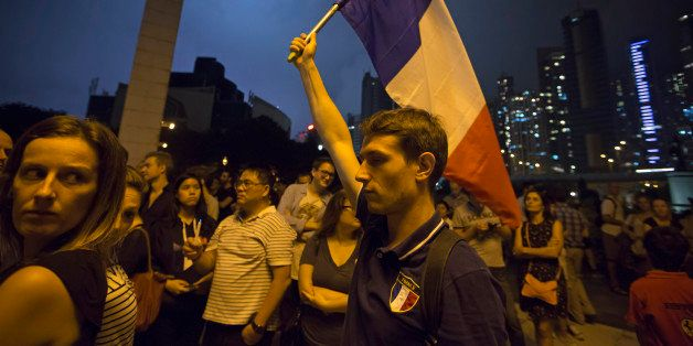 A man carries French national flag as people gather in Hong Kong, Saturday, Nov. 14, 2015, to mourn for the victims killed in