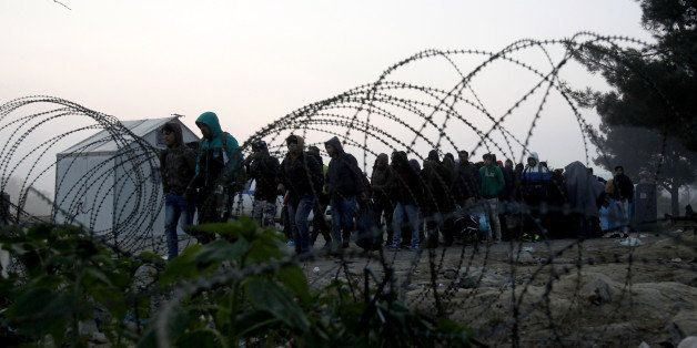 People cross the border from Greece into Macedonia, near the southern Macedonian town of Gevgelija, early Saturday, Nov. 14,