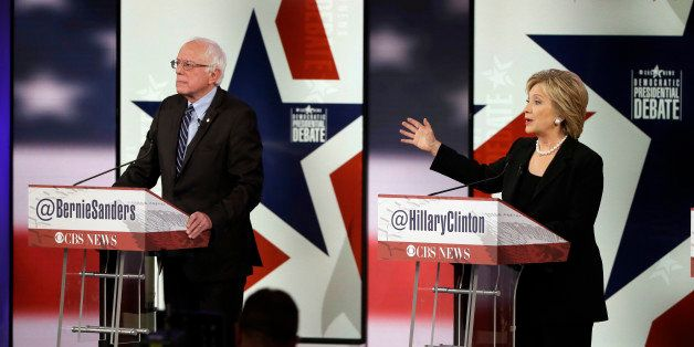 Hillary Rodham Clinton, right, makes a point as Bernie Sanders listens during a Democratic presidential primary debate, Satur