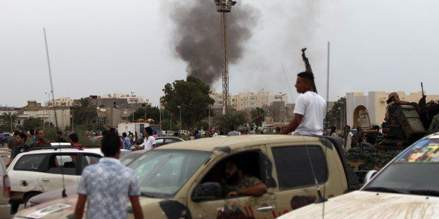 Smoke billows from the site of shelling by anti-governemnt forces as Libyans attended a protest against a national unity gove