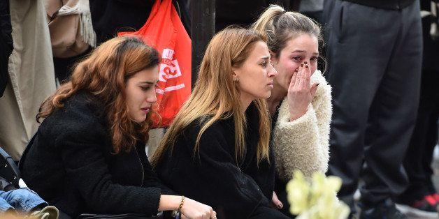 PARIS, FRANCE - NOVEMBER 16: Members of the public stand still at La Belle Equipe cafe on Rue de Charonne, one of the places attacked by terrorists, on November 16, 2015 in Paris, France. Countries across Europe will join France, currently observing three days of national mourning, for a one minute-silence today in an expression of solidarity with the victims of the terrorist attacks, which left at least 129 people dead and hundreds more injured. (Photo by Jeff J Mitchell/Getty Images)