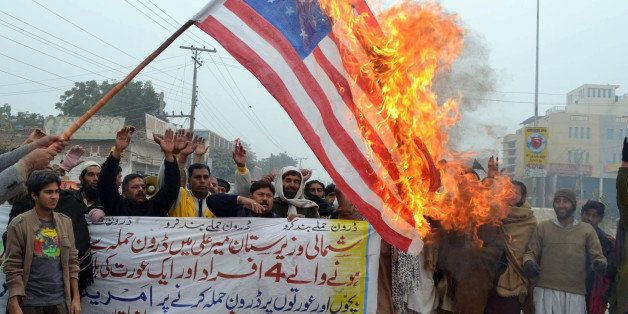 Pakistani demonstrators shout slogans beside a burning US flag during a protest in Multan on January 3, 2013, against the dro