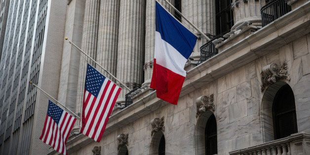 NEW YORK, NY - NOVEMBER 16:  French and U.S. flags fly at half mast outside the New York Stock Exchange in honor of the victi