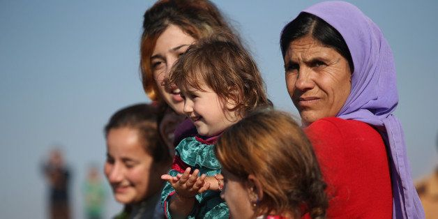 DEREK, SYRIA - NOVEMBER 13:  Yazidi refugees watch as othes celebrate news of the liberation of their homeland of Sinjar from
