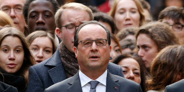 French President Francois Hollande stands among students during a minute of silence in the courtyard of the Sorbonne Universi