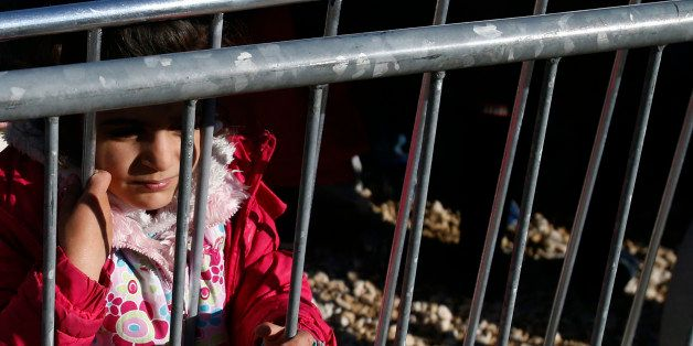 A migrant girl looks through the fence waiting to register with the police, in a refugee center in the southern Serbian town