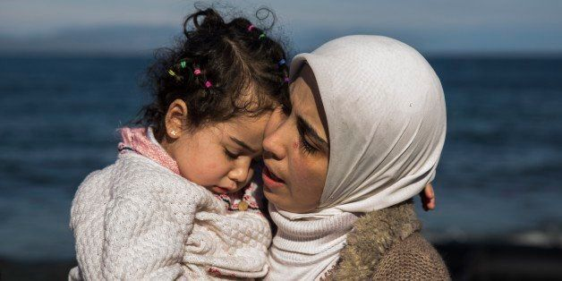 A Syrian mother hugs her child after they arrived from Turkey at the Greek island of Lesbos  on an overcrowded inflatable boa