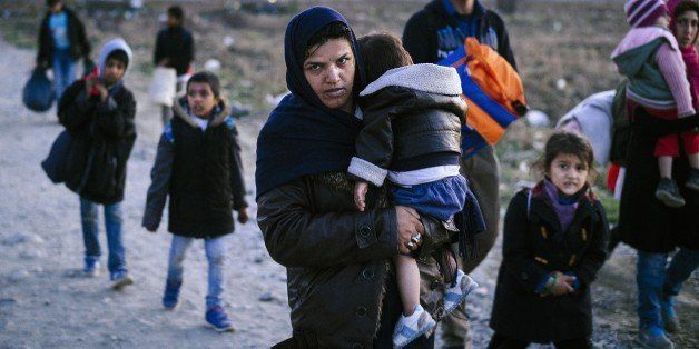 A woman carries a child as migrants and refugees walk near Gevgelija, after crossing the Greece-Macedonia border, on November