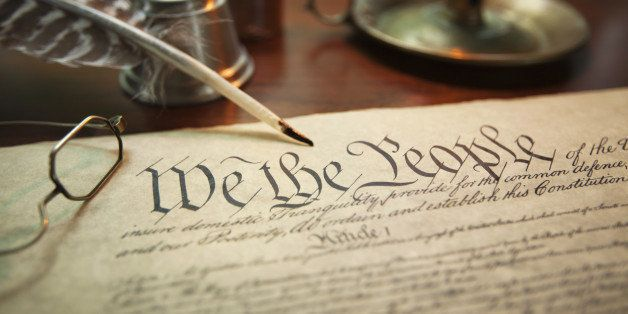 Selective focus image of the United States Constitution with quill pen, glasses and candle holder