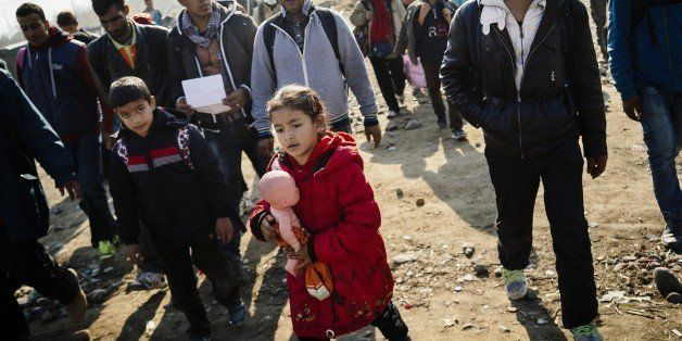 A girl carries her doll as she along with other migrants and refugees walk after crossing the Greek-Macedonian border near Ge