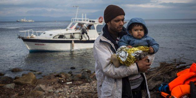 A father holds his baby after their arrival on a vessel with other refugees and migrants from the Turkish coast to the northe