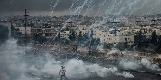 JERUSALEM, Nov. 6, 2015 -- Palestinian protesters evade from a shower of tear gas cylinders shot by Israeli security forces d