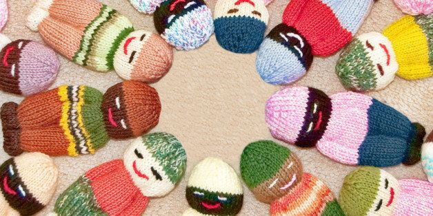 Knit toy children dolls with many colors of multiculturalism within the faces.